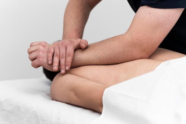 Mann, der eine rückenmassage durch physiotherapeuten gegeben wird