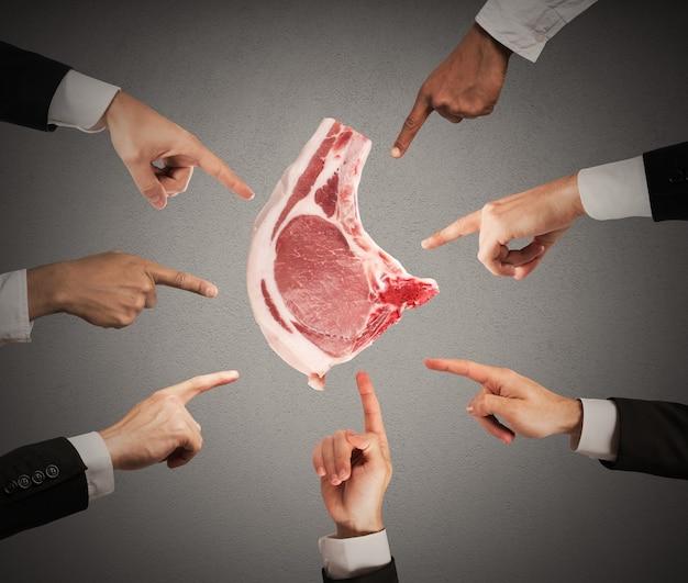Mann, der eine scheibe rohes rindfleisch hält, während hände anklagend zeigen