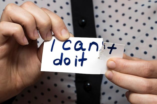 Mann, der eine schere verwendet, um das wort zu entfernen, kann nicht lesen, ich kann es für selbstvertrauen, positive einstellung und motivation tun.
