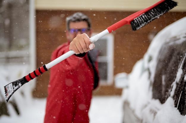 Mann, der eine schneebürste in richtung hält