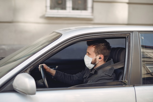 Mann, der eine schutzmaske sitzt, die in einem auto sitzt