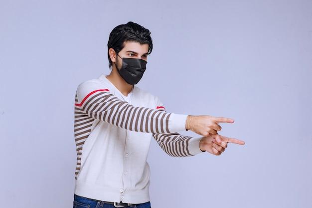 Mann, der eine schwarze maske trägt, die auf irgendwo zeigt.