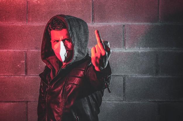 Mann, der eine sicherheitsmaske gegen das virus trägt, ficken zeichen