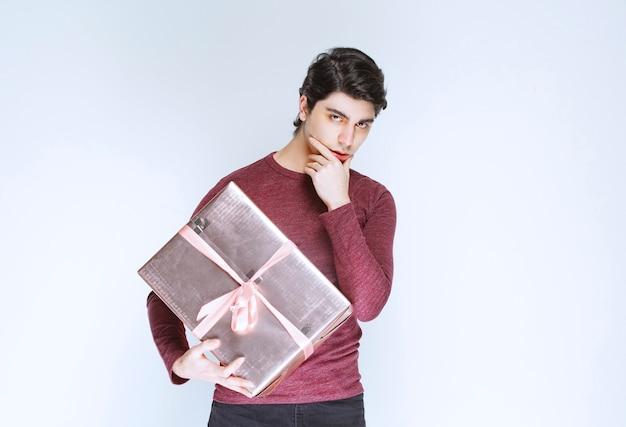 Mann, der eine silberne rosa geschenkbox hält und denkt.