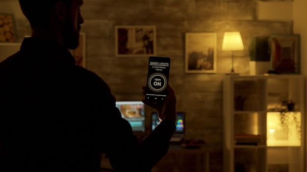 Mann, der eine smart-lights-app verwendet, um das licht im wohnzimmer einzuschalten. intelligente technologie und anwendung