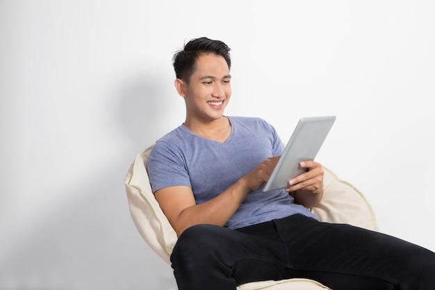 Mann, der eine tablette beim sitzen auf dem stuhl hält