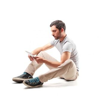 Mann, der eine tablette sitzt und verwendet