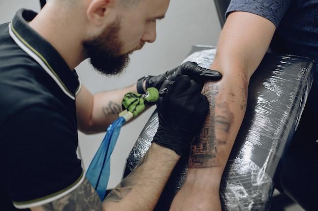 Mann, der eine tätowierung in einem tätowierungssalon tut