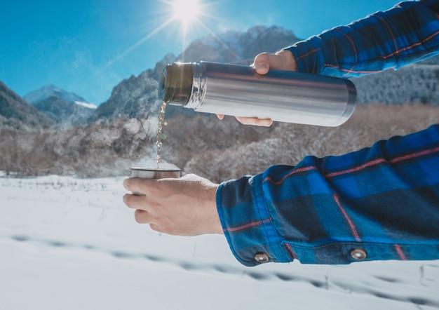 Mann, der eine thermoskanne auf einem schneebedeckten berg hält