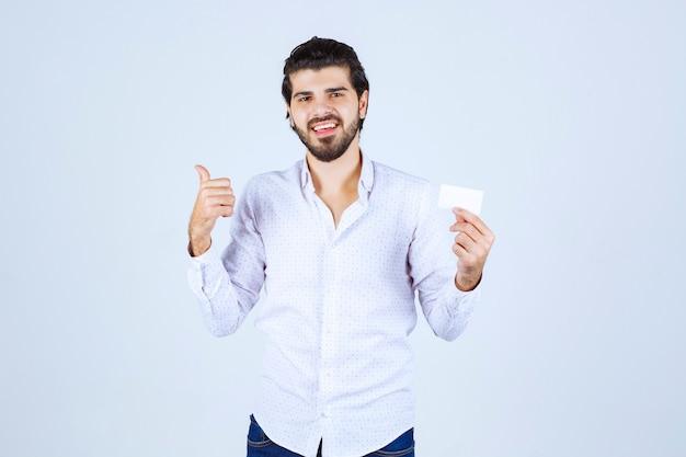 Mann, der eine visitenkarte hält und auf jemanden in der nähe zeigt