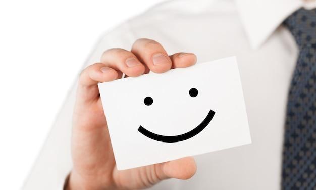 Mann, der eine visitenkarte mit glücklichem smiley hält