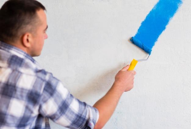 Mann, der eine wand mit farbenrolle malt