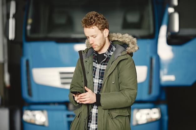 Mann, der eine warme grüne jacke trägt. lkw in garage geparkt. logistikprobleme lösen