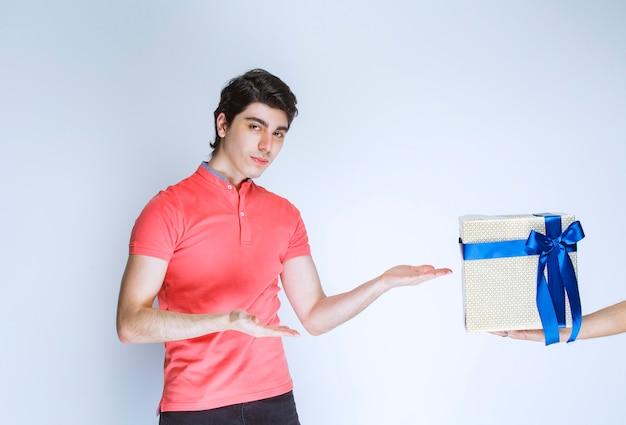 Mann, der eine weiße geschenkbox empfängt und darauf zeigt.