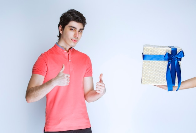 Mann, der eine weiße geschenkbox empfängt und daumen oben zeigt. Kostenlose Fotos