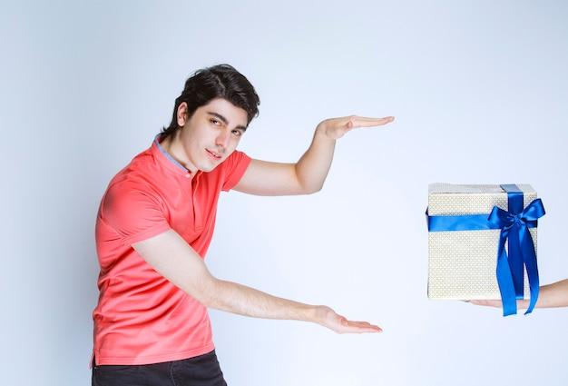 Mann, der eine weiße geschenkbox empfängt und hält, die mit blauem band mit beiden händen gewickelt wird