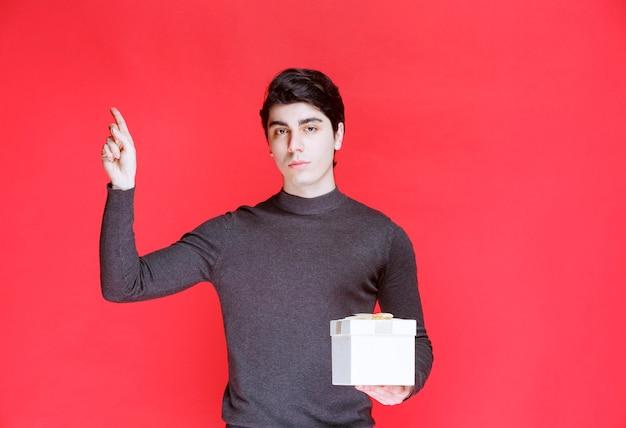 Mann, der eine weiße geschenkbox hält und auf irgendwo zeigt