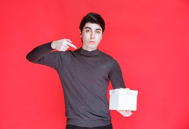 Mann, der eine weiße geschenkbox hält und darauf zeigt