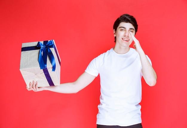 Mann, der eine weiße geschenkbox hält und jemanden anruft