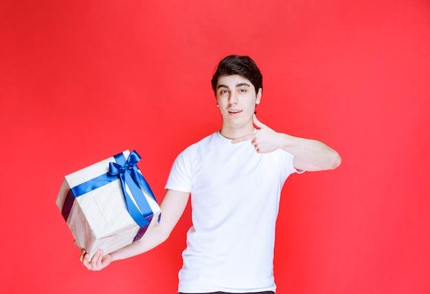 Mann, der eine weiße geschenkbox hält und positives handzeichen zeigt