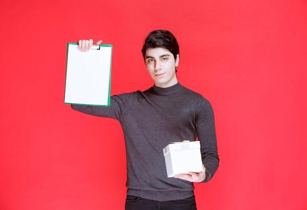 Mann, der eine weiße geschenkbox hält und um eine unterschrift bittet