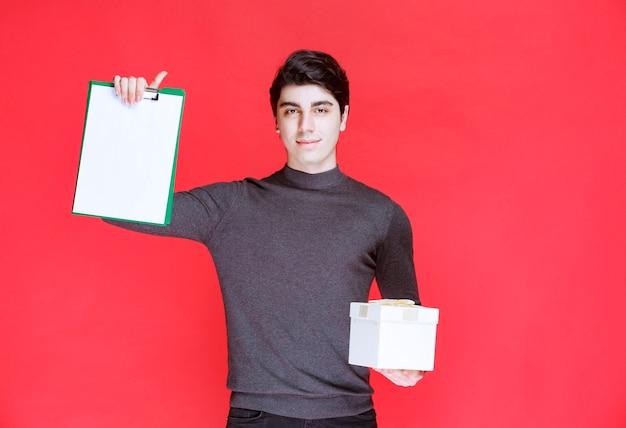 Mann, der eine weiße geschenkbox hält und um eine unterschrift bittet Kostenlose Fotos