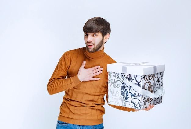Mann, der eine weiße geschenkbox mit blauen mustern hält und sich überrascht zeigt.