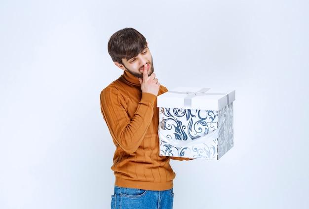 Mann, der eine weiße geschenkbox mit blauen mustern hält und um stille bittet oder über etwas zögert.