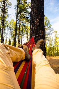 Mann, der einen alternativen freien lebensstil in waldwäldern genießt, der auf einer hängematte liegt und sich beim blick in den blauen himmel entspannt - reiseleute und freizeitpark im freien - umwelt natur