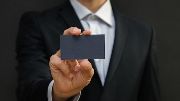 Mann, der einen anzug trägt, der weiße visitenkarte auf schwarzem wandhintergrund hält