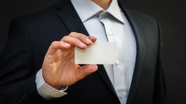 Mann, der einen anzug trägt, der weiße visitenkarte auf schwarzer wand hält