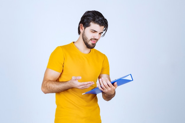 Mann, der einen blauen ordner hält und die berichte überprüft.