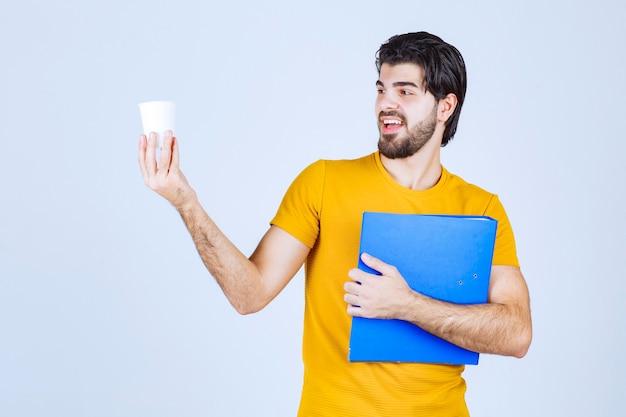Mann, der einen blauen ordner und eine kaffeetasse hält.