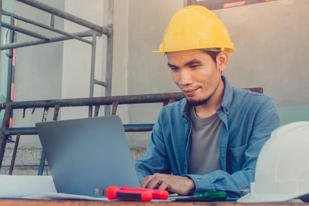 Mann, der einen computer verwendet, der auf der baustelle mit hartem helm arbeitet