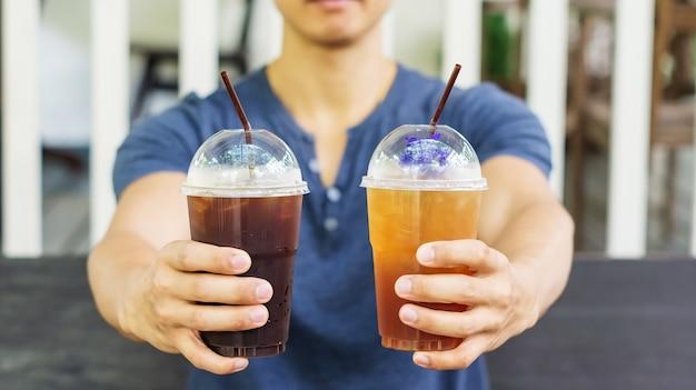 Mann, der einen eiskaffee und einen eistee in einem café trinkt.