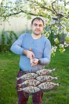Mann, der einen gegrillten fisch in einem stahlgitter hält