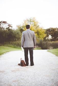 Mann, der einen geschäftsanzug trägt, der auf einem weg steht, während er die bibel hält
