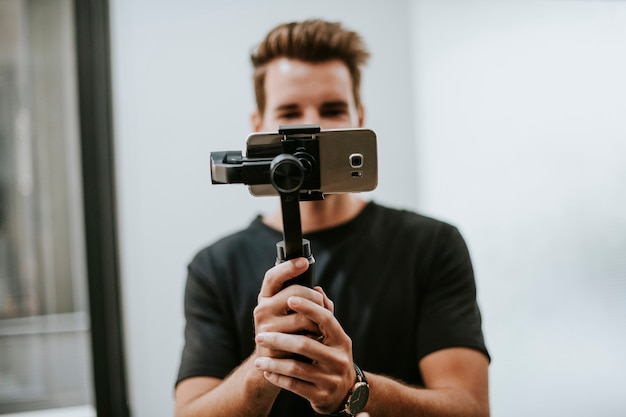 Mann, der einen gimbal mit einem telefon hält Premium Fotos