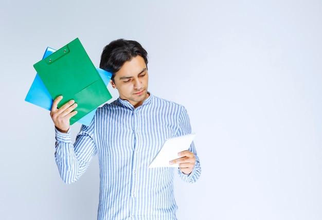 Mann, der einen grünen berichtsordner hält und denkt. foto in hoher qualität