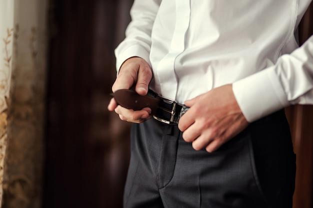 Mann, der einen gürtel anlegt, geschäftsmann, politiker, männerstil, männliche handnahaufnahme, amerikanischer geschäftsmann, europäischer geschäftsmann, ein geschäftsmann aus asien, leute, geschäft, mode und kleidungskonzept