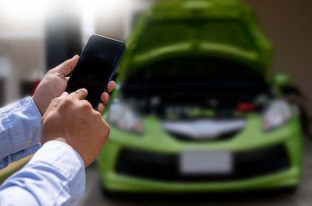 Mann, der einen handyanruf zur unterstützung verwendet helfen sie mit einer defekten autounterstützungsstoppauto-panne