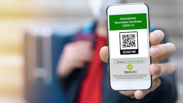 Mann, der einen internationalen impfausweis covid-19-qr-code auf dem smartphone zeigt