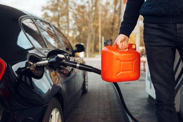 Mann, der einen kanister an der tankstelle hält, kraftstoff einfüllen. benzintanken, benzin- oder dieseltankservice, benzintanken