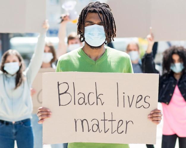 Mann, der einen karton mit schwarzem lebensmateriezitat hält