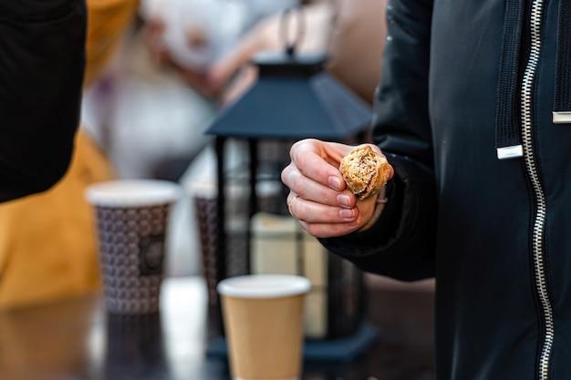 Mann, der einen keks in seiner hand, cafeteriatisch im freien mit pappbechern und einer laterne, nahaufnahme hält