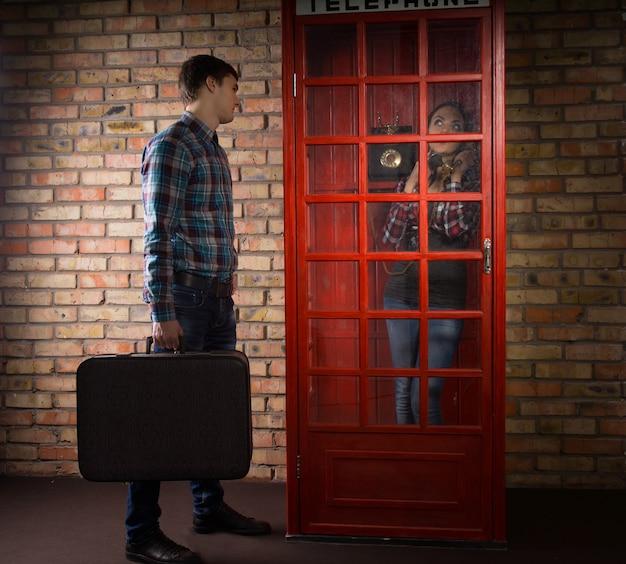 Mann, der einen koffer hält und vor einer telefonzelle auf seine frau wartet, während sie drinnen steht und am telefon plaudert, ohne seine anwesenheit zu bemerken
