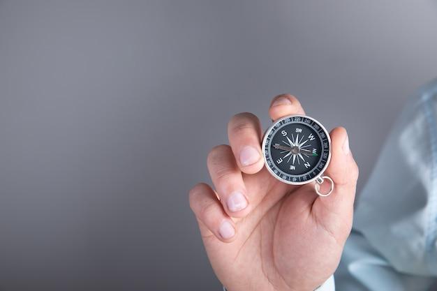 Mann, der einen kompass in seiner hand auf einer grauen oberfläche hält