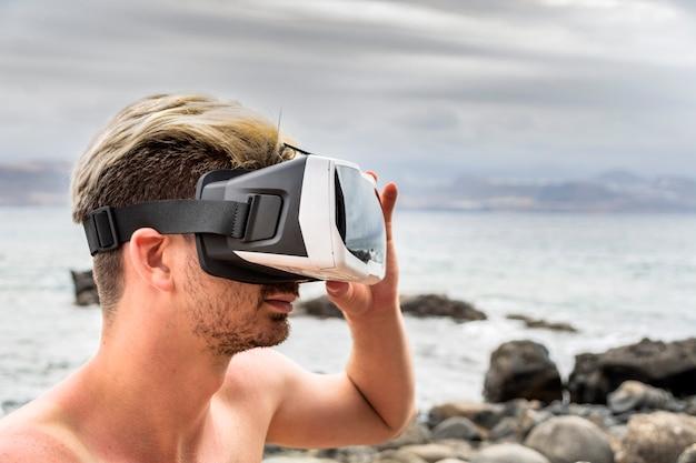 Mann, der einen kopfhörer der virtuellen realität auf dem strand verwendet