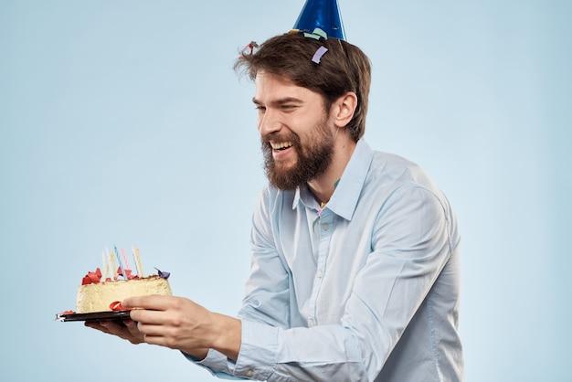 Mann, der einen kuchen mit kerzen hält