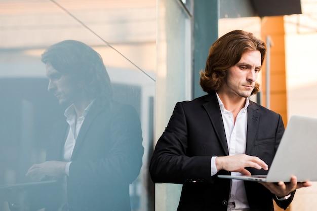 Mann, der einen laptop im freien mit kopienraum verwendet